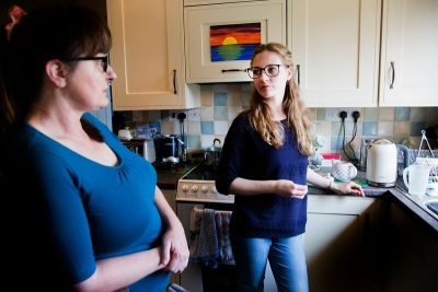 Young Adult Carer Emily chats to her mum in their kitchen.